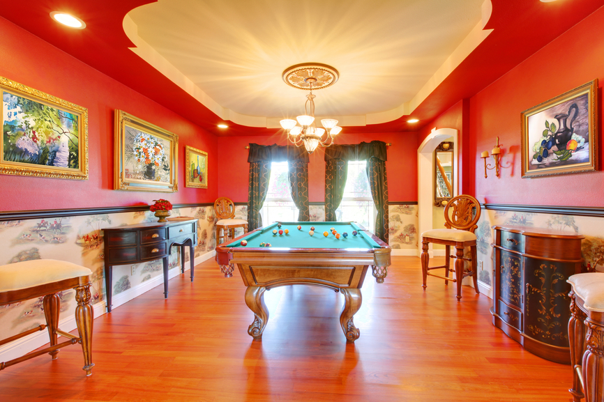 Red billiard luxury room with play pool and cherry hardwood.